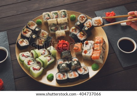 Japanese food restaurant, sushi maki gunkan roll plate or platter set. Hand take roll. Set for two with chopsticks, ginger, soy, wasabi. Sushi at rustic wood background and black stone. POV at black.  - stock photo