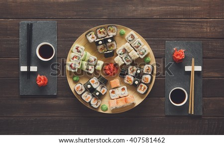 Japanese food restaurant, sushi maki gunkan roll plate or platter set. Set for two with chopsticks, ginger, soy, wasabi. Sushi at rustic wood background and black stone. Top view at wood - stock photo