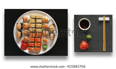 Japanese food restaurant, sushi maki gunkan roll plate or platter set. Set with chopsticks, ginger, soy sauce and wasabi. Sushi at black stone isolated at white background. Top view, Flat lay. - stock photo