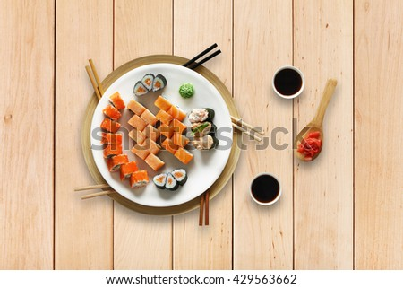 Japanese food restaurant, sushi maki gunkan roll plate or platter set. Set with chopsticks, ginger, soy, wasabi. Sushi at wooden planks background. Top view, flat lay. - stock photo