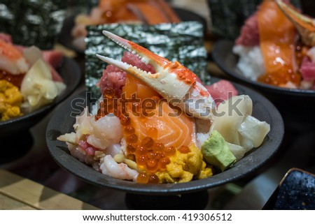Japanese Food - seafood don set. The uni don (sea urchin rice bowl) is served with uni, scallop, king crab, salmon eggs, crab stick and octopus and tuna toro on vinegar rice - stock photo