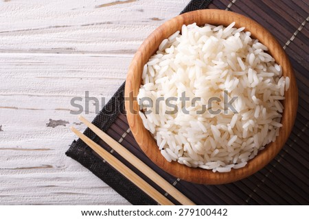 Japanese food: steamed rice in a wooden bowl and chopsticks. horizontal view from above  - stock photo