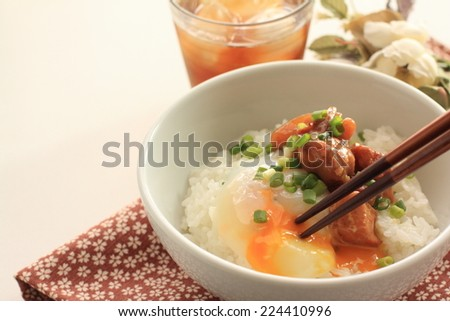 Japanese food, Yakitori and porched egg on rice with iced tea on background