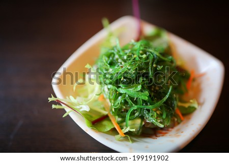 Japanese foods include sushi, nigiri, sashimi, served on small plate on a wooden background - stock photo