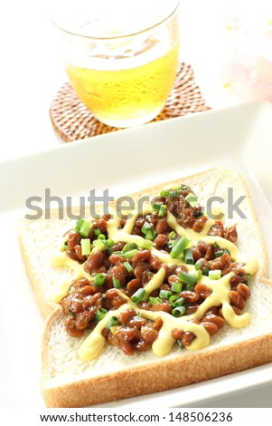 Japanese fusion food, Natto and mayonnaise on toast with green tea and flower on background - stock photo