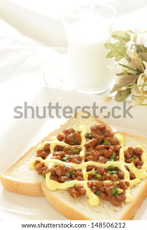 Japanese fusion food, Natto and mayonnaise on toast with milk and flower on background - stock photo
