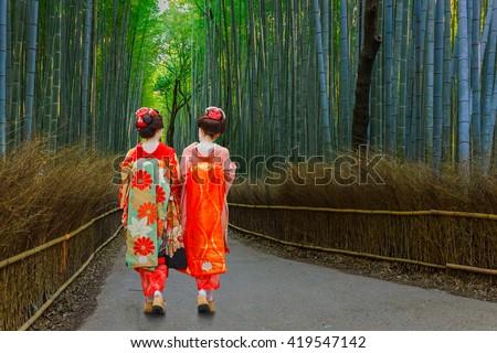 Japanese Geisha at Chikurin-no-Michi (Bamboo Grove) in Arashiyama in Kyoto   - stock photo