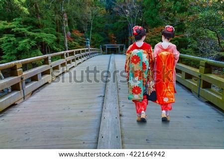 Japanese Geisha on a Bridge at Ise-jingu (Naiku) Shrine in Ise, Mie Prefecture, Japan - stock photo