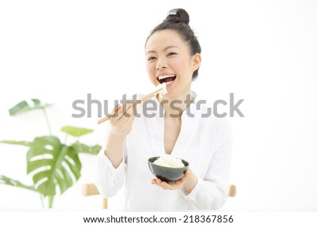 Japanese girl eating rice with sticks, isolated on white background