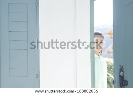 Japanese girl leaning out head from door - stock photo
