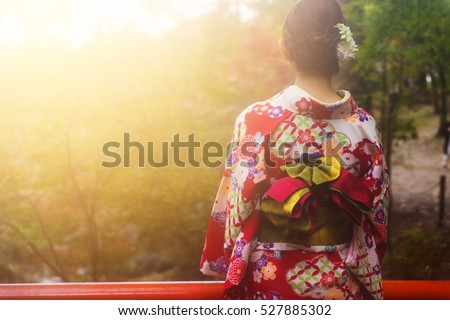 Japanese girl with traditional kimono enjoy autumn colors during sunset at Fushimi Inari temple, Kyoto, Japan
