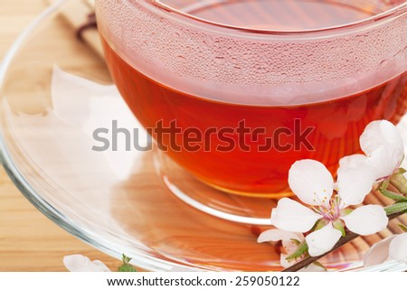 Japanese green tea and sakura branch over mat and bamboo table - stock photo