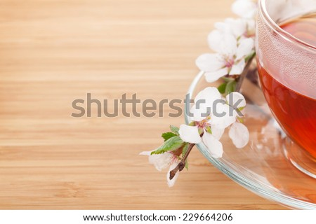 Japanese green tea and sakura branch over mat and bamboo table with copy space - stock photo