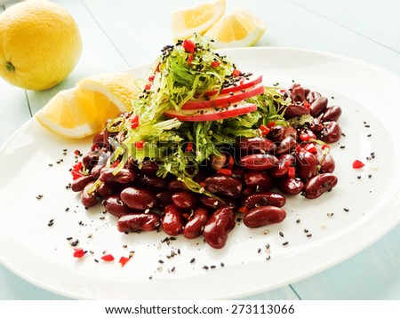 Japanese kaiso salad with red beans, lemon and red pepper. Shallow dof. - stock photo