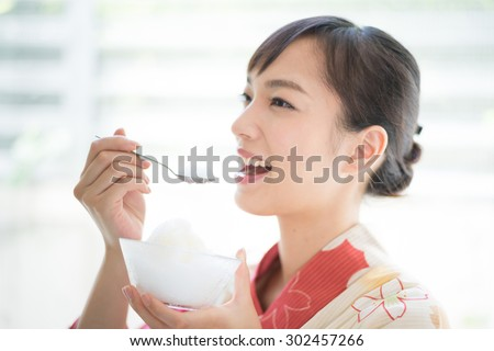 "Japanese kimono woman eating Japanese shaved ice dessert ""Kakigori"""
