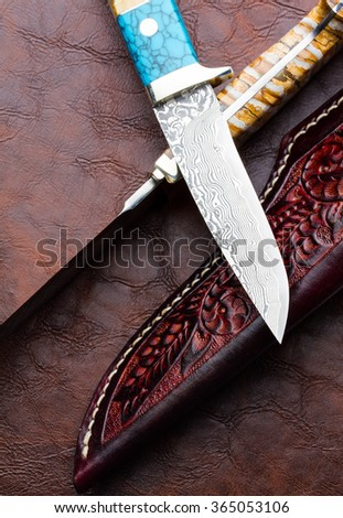 japanese Knife and Leather sheath knife on brown leather  background
