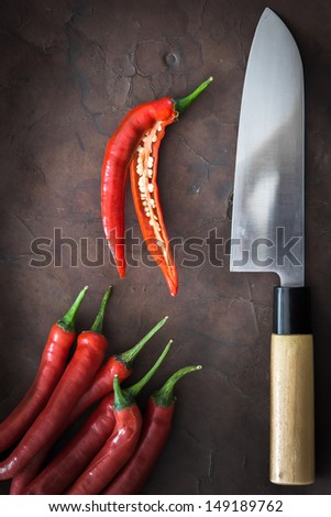 japanese Knife with Chili on old Leather - stock photo