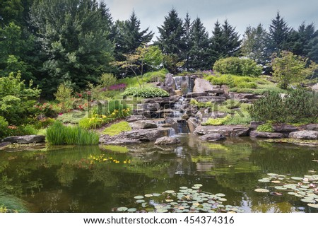 Japanese lake in Grand Rapids, Michigan, United States Calm water of a lake with a waterfall in a japanese garden, surrounded by trees and plants. Meijer Garden, Grand Rapids, Michigan, United States. - stock photo