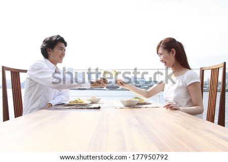 Japanese man and Japanese woman drinking a toast on the terrace - stock photo