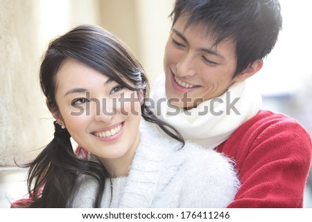 Japanese man embracing his girlfriend - stock photo