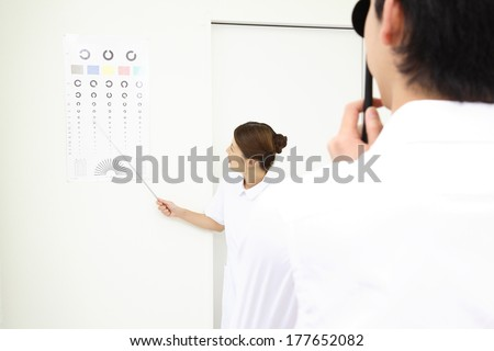 Japanese man having an eye test taken and a nurse - stock photo