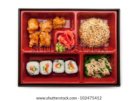 Japanese Meal in a Box (Bento) - Chuka Salad, Fried Rice with Veggies, Sushi Roll, Tori Karagi (breaded chicken) - stock photo