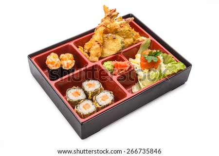 Japanese Meal in a Box (Bento) isolated on white background - classic salad, breaded shrimp and zucchini, sushi and rolls - stock photo