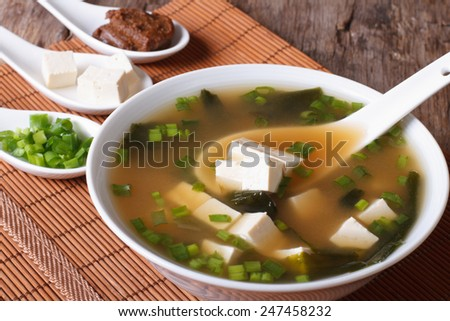 Japanese miso soup in a white bowl with a spoon on a table close-up. vertical   - stock photo