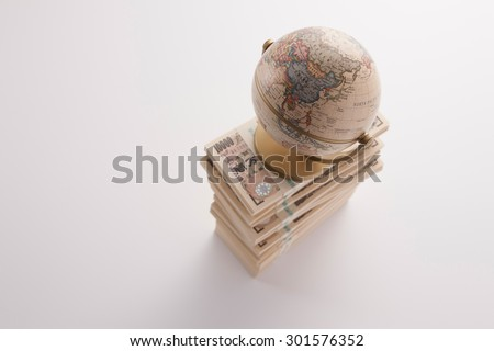 Japanese money and terrestrial globe - stock photo