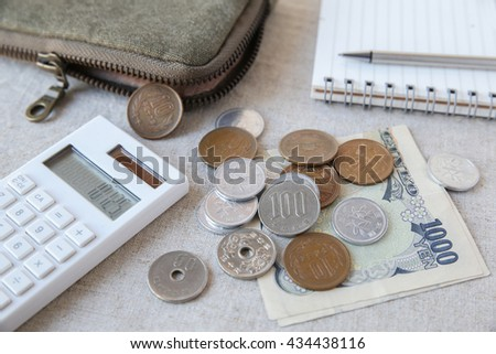 Japanese money, Yens wtih calculator, notebook and small money pouch,selective focus on 100 yen coin - stock photo
