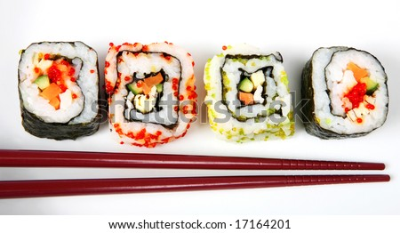 Japanese nori-wrapped futomaki (at each end) and rice-wrapped uramaki (California roll) sushi rolls on a white plate with chopsticks - stock photo