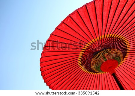 Japanese red umbrella against clear blue sky - stock photo
