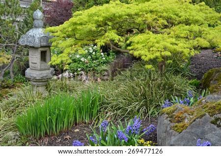 Japanese shrine in lush green spring garden - stock photo