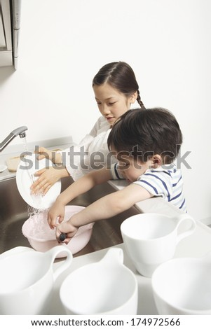 Japanese Siblings help do the dishes - stock photo
