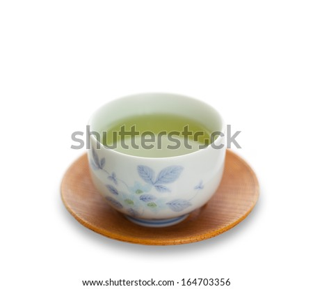 Japanese simmered green tea in a ceramic cup on a traditional saucer isolated on white with copy space
