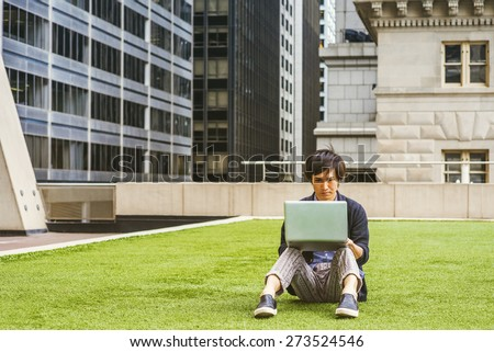Japanese student studying in New York. Wearing patterned shirt, black sweater, casual pants, leather shoes, a young guy sitting on green lawn in business district, reading, working on laptop computer. - stock photo