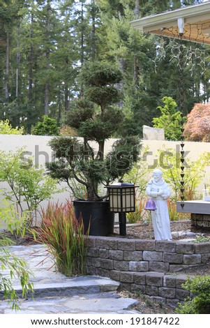 Japanese  style landscaping. View of decorative tree, lantern and small statue