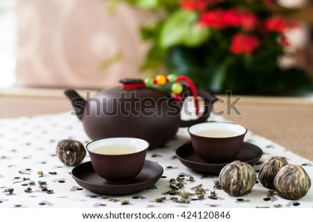 Japanese style tea set with small cups and ceramic pot with green tea leaves and balls bundle - stock photo