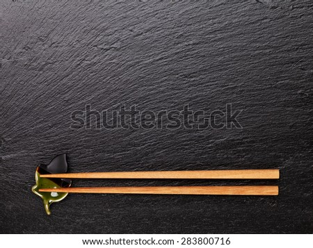 Japanese sushi chopsticks on black stone background. Top view with copy space - stock photo