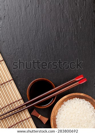 Japanese sushi chopsticks over soy sauce bowl and rice on black stone background. Top view with copy space - stock photo