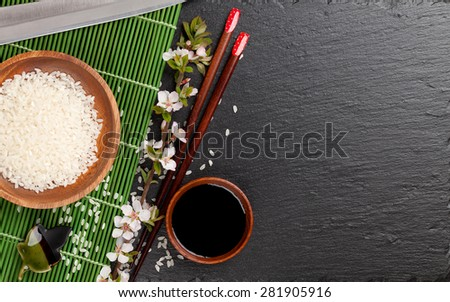 Japanese sushi chopsticks, soy sauce bowl, rice and sakura blossom on black stone background. Top view with copy space - stock photo
