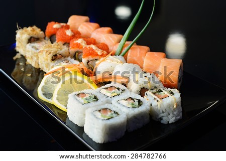 Japanese sushi on a black plate. - stock photo