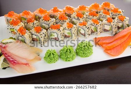 Japanese tasty sushi set on a white plate over black background - stock photo