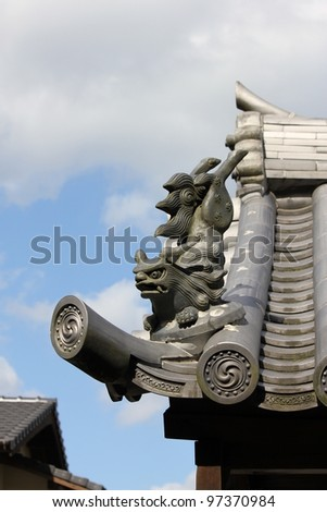 Japanese temple roof with stone statue - stock photo