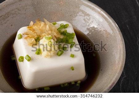 Japanese tofu, Japanese soft cold tofu with sauce in a dish on dining table - stock photo