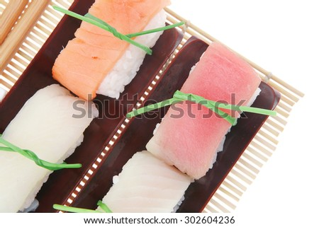 Japanese traditional cuisine - Different Types of Nigiri Sushi : Tuna (maguro) Salmon (sake) and Eel (unagi) with Wasabi and Ginger on bamboo mat isolated over white background - stock photo
