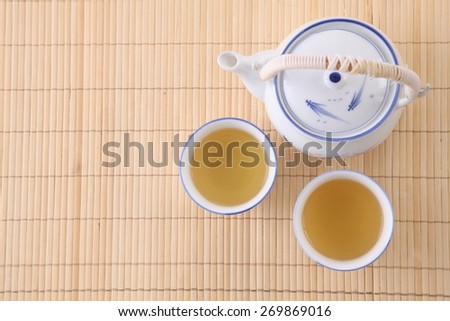 Japanese white tea pot on the bamboo mat - stock photo