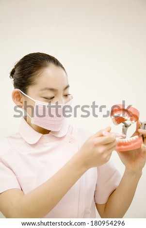 Japanese woman dentist holding dentures