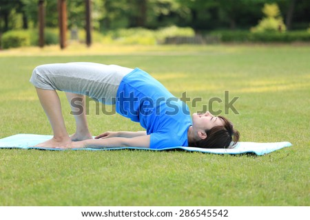 Japanese woman doing yoga Bridge Pose - stock photo