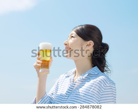 Japanese woman drinks on sky background - stock photo